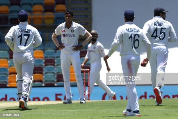 Indian players run towards their fielding positions at the end of paceman Navdeep Saini's over on day one of the fourth cricket Test match between...