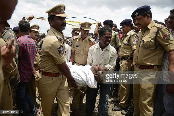 Indian police and a family member carry the body of a school bus driver towards an ambulance at the site of the collision between a school bus and a...