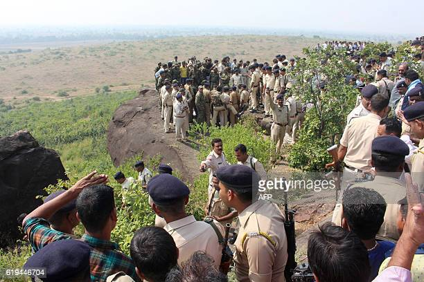 Indian police and bystanders gather at the site where eight SIMI activists who escaped from Central Jail in Bhopal were killed by Special Task Force...