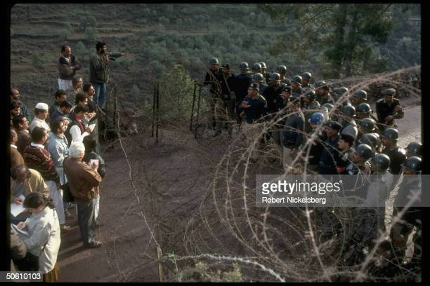 Indian Police and members of the world press talk and observe each other over a coil of barbed wire as the reporters try to cover a Jammu Kashmir...