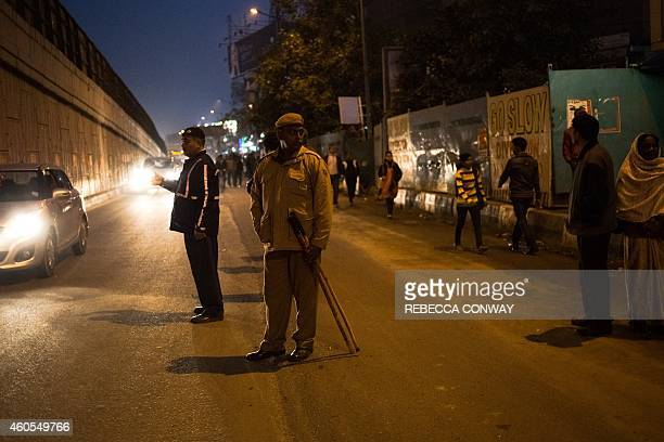 Indian police and traffic police direct cars and stand guard during a vigil to mark the second anniversary of the fatal gangrape of a student in the...