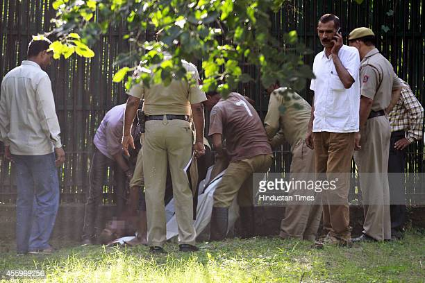 Indian police and zoo personnel stand over the body of a 20 year youth who was killed by a white tiger after he fell inside its enclosure at the...