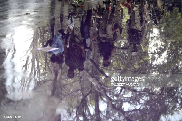 Indian police are reflected in a puddle during a protest by Kashmiri government teachers in Srinagar on July 17 2018 Dozens of government employees...