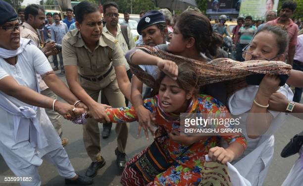 TOPSHOT Indian police arrest activists from the Social Unity Centre of India organisation as they block a road during a protest against a gang rape...