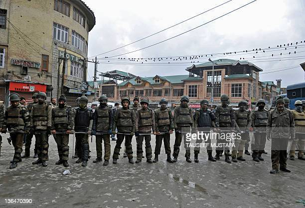 Indian police block a road as Jammu and Kashmir Liberation Front supporters during a protest against the killing of an 18 year old student by...