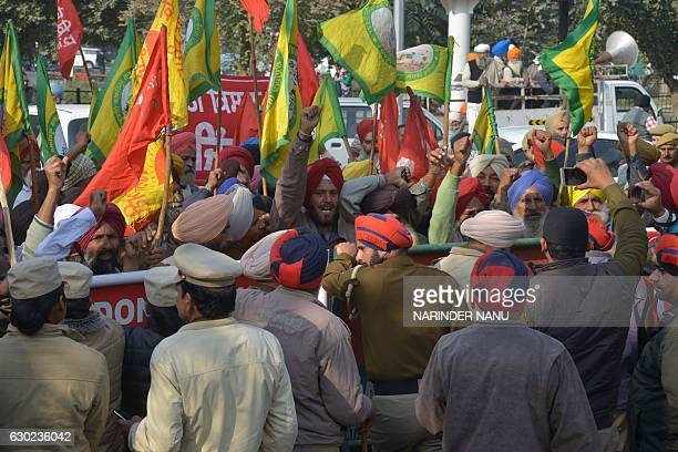 Indian police block farmers as they march towards the residence of Cabinet Minister Bikram Singh Majithia during a protest in Amritsar on December 19...