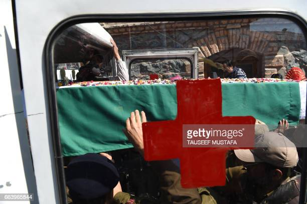 TOPSHOT Indian police carry the coffin of a slain colleague from a ambulance before a wreath laying ceremony in Srinagar on April 3 2017 A policeman...