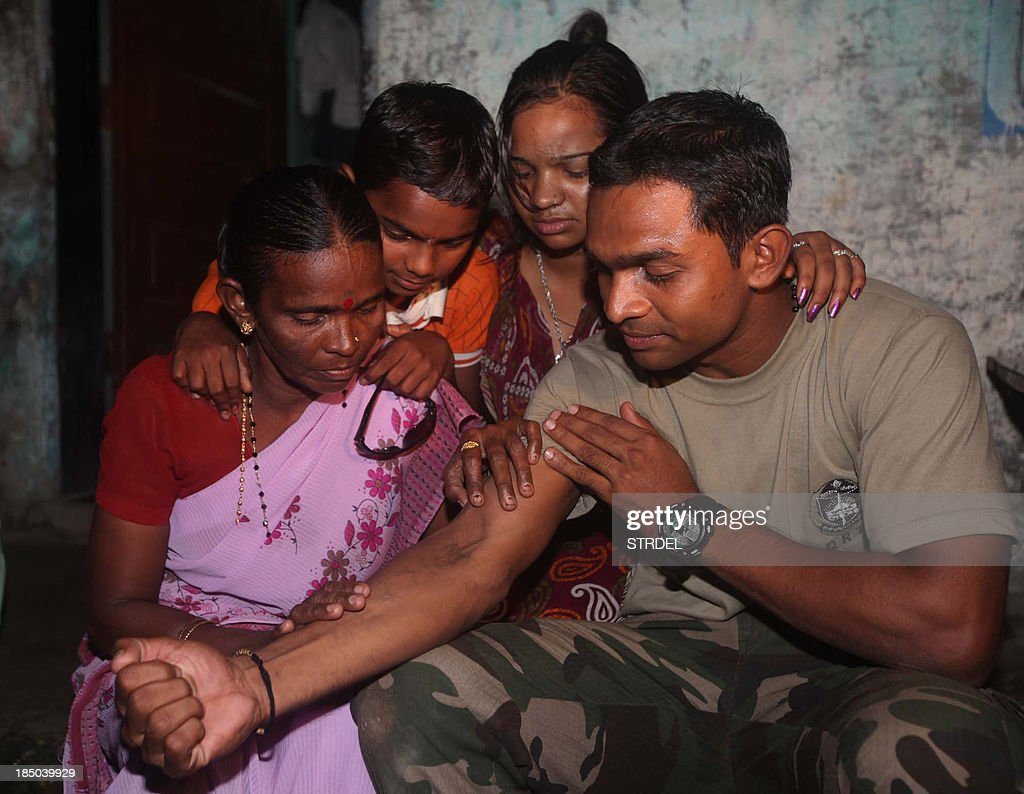 Indian police commando, Ganesh Raghunath Dhangade (R), shows a tatoo to his family in Thane district on the outskirts of Mumbai on October 16, 2013. Dhangade who got lost as a child at a crowded railway station was reunited with his family after 24 years -- thanks to a tattoo on his arm. Dhangade was separated from his parents in 1989 aged just six when they were boarding a train. He ended up on his own in Mumbai, where he was cared for by a fisherman and then at two orphanages.