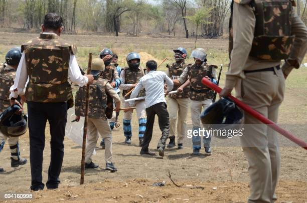 Indian police detain a protesting farmer in Fanda village on the outskirts of Bhopal in Madhya Pradesh state on June 9 2017 Thousands of farmers in...