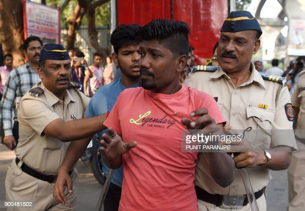 Indian police detain two youths after a Republican Party of India protest turned violent in Mumbai on January 2 2018 India's Republican Party...