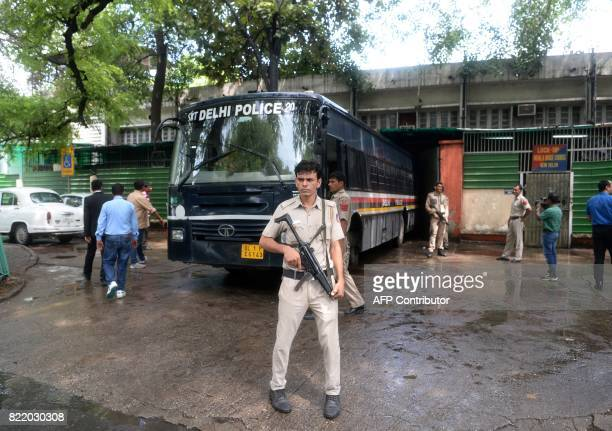 Indian police escort a police bus carrying arrested All Parties Hurriyat Conference leaders at Patiala House Court in New Delhi on July 25 2017...