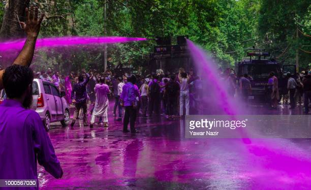 Indian police fire a jet of dyed water from their water cannon at Kashmiri government teachers during a protest against the government on July 17...