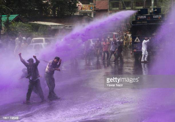 Indian police fire a jet of dyed water with water cannons at Kashmiri government employees during a protest against the government on September 09,...