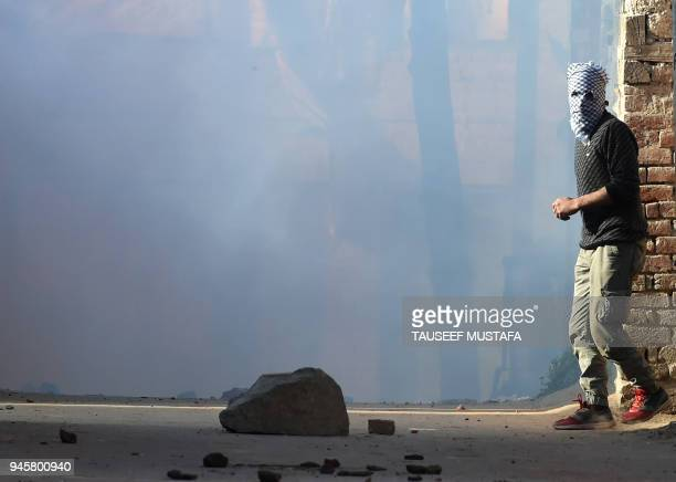 TOPSHOT Indian police fired tear smoke shells during a clash with Kashmiri protesters against recent killings in Srinagar on April 13 2018 The brutal...