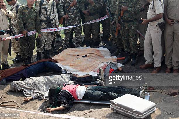 Indian police gather alongside the bodies of SIMI activists who escaped from Central Jail in Bhopal and were killed by Special Task Force police at...
