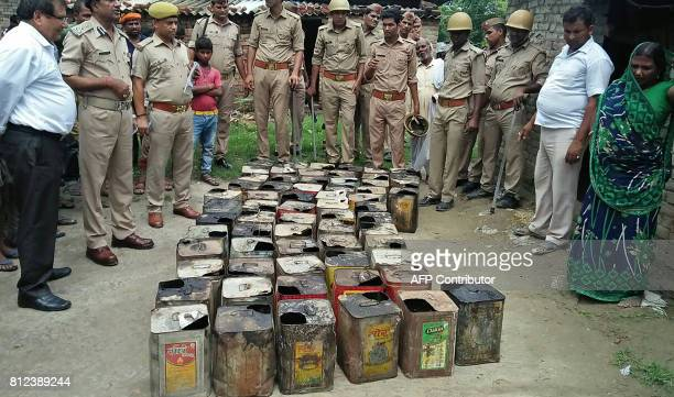 Indian police gather around containers of bootleg alcohol recovered in a raid after multiple deaths from alcohol poisoning in Azamgarh village in...