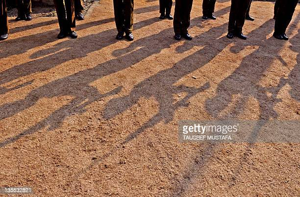 Indian police officer stand during a wreath laying ceremony for a colleague who was killed during a suspected militant attack late on December 11 in...