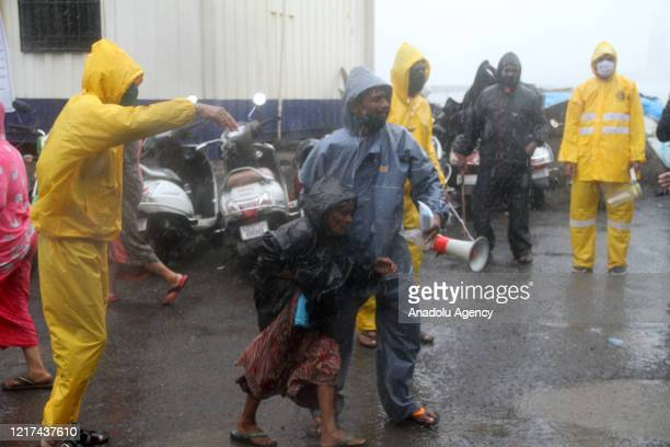 Indian Police officers help a woman before Cyclone Nisarga hits Mumbai, India on June 03, 2020. A storm in the Arabian Sea off India's west coast...