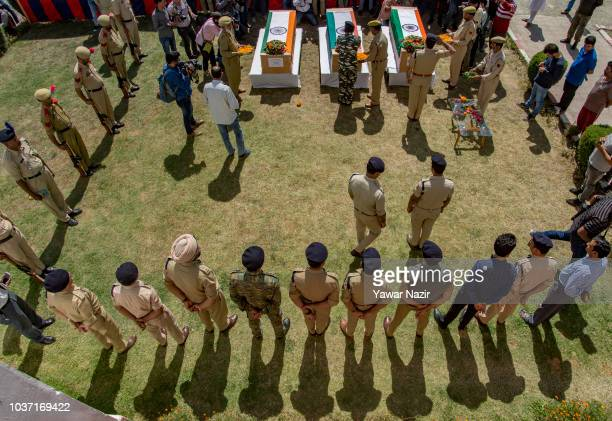 Indian policemen and their officers carry the coffins containing the bodies of their comrades killed by suspected militants after a wreath laying...
