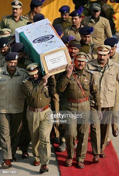 Indian police officers of Central Reserve Police Force carry the coffins of their dead colleagues during a wreath laying ceremony on December 31 2009...