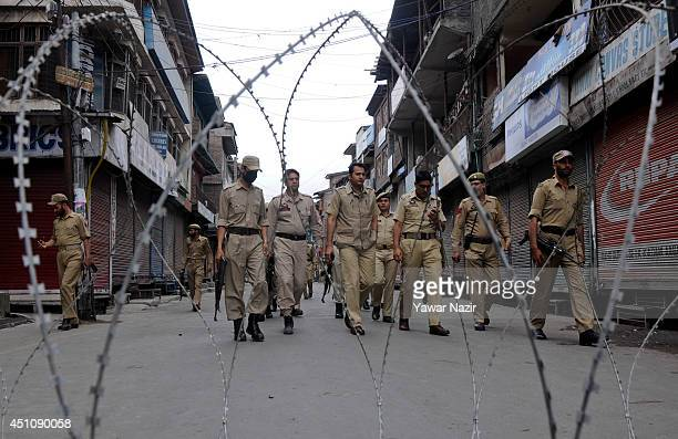 Indian police officers patrol the main city during restrictions on June 23 2014 in Srinagar the summer capital of Indian administered Kashmir India...