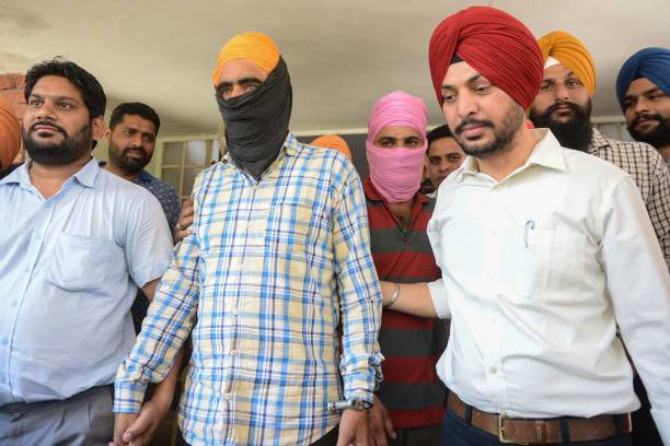Indian police officers with the State Special Operation Cell escort alleged heroin smugglers Ranjit Singh and Gursewak Singh during a press...
