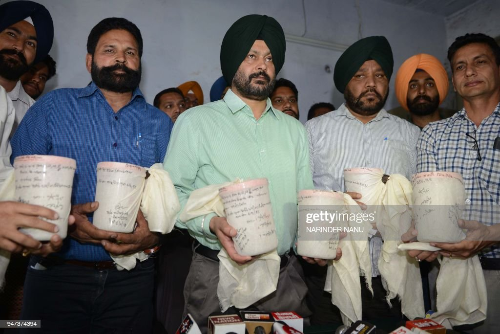 Indian police officers with the State Special Operation Cell pose with seven kilograms of heroin recovered from alleged smugglers during a press...