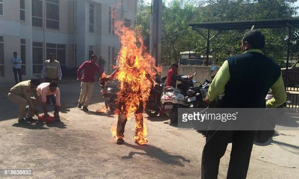 TOPSHOT Indian police officials begin efforts to save Bhanubhai Vankar who set himself on fire outside the Patan district collector's office at Patan...