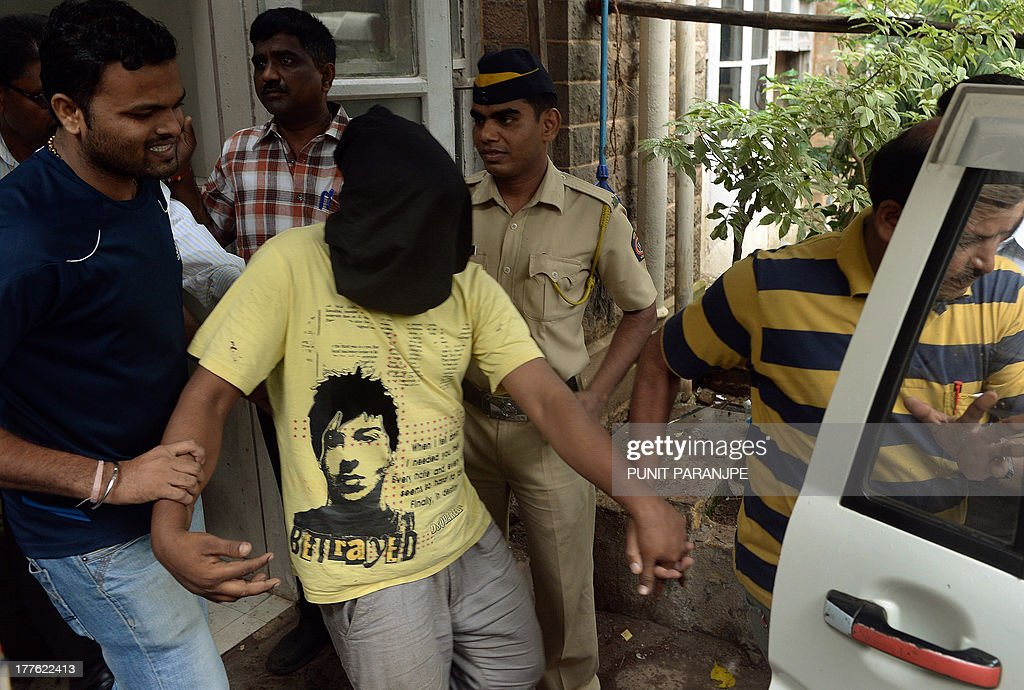 Indian police officials escort a suspect (C) in the gang-rape of a female photographer after his appearance at a court in Mumbai on August 25, 2013. Mumbai police arrested a fourth suspect over the gang-rape of a photographer, a crime that reignited anger about women's safety in India following a similar attack last year.