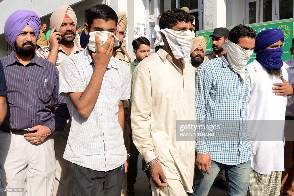 Indian police officials from the CounterIntelligence Wing escort suspected Pakistani national smugglers Mohammed Aqib Khan Razif Mohammed and Indian..