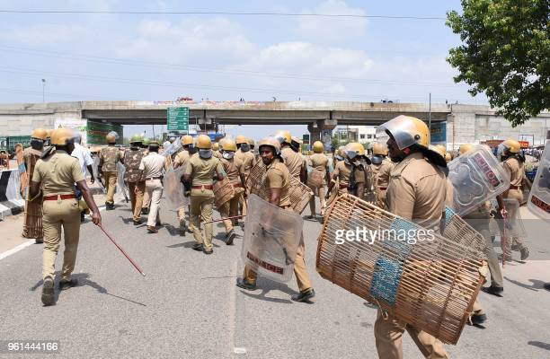 TOPSHOT Indian police officials run towards protestors in the southern Indian city of Tuticorin some 600 kilometres south of Chennai on May 22 during...
