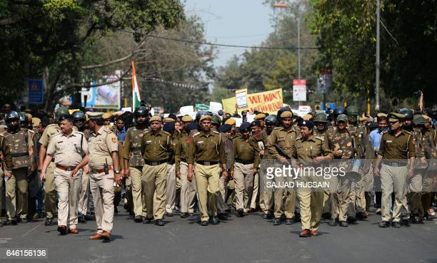 Indian police officials walk ahead of students holding placards during a protest march outside Delhi University against the Akhil Bharatiya Vidyarthi...