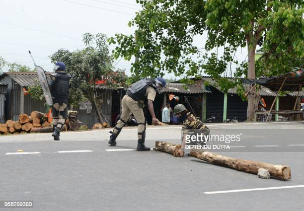 Indian police personal remove wooden logs from a road as supporters of Bharatiya Janata Party protest over the ruling party Trinamul Congress at...