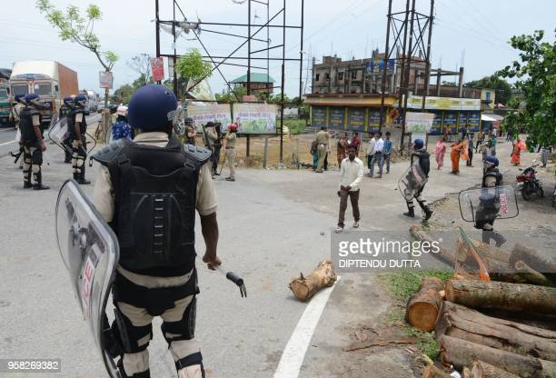 Indian police personal stand guard as supporters of Bharatiya Janata Party block the National Highway 31 during a protest allegations over the ruling...