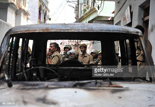 Indian police personnel are seen through the remains of a vehicle which was burnt during communal violence at Begum Bazar in Hyderabad on March 30...
