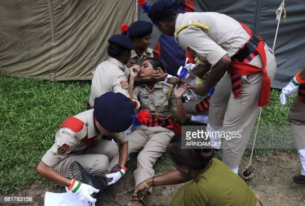 TOPSHOT Indian police personnel assist a colleague after she fainted during a passing out ceremony at a police training academy in Agartala on May 11...