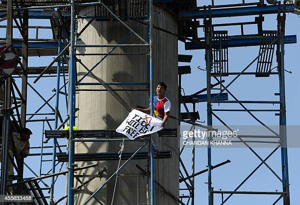 Indian police personnel climb scaffolding in an attempt to detain an exiled Tibetan youth as he protests against a visit to India by Chinese...