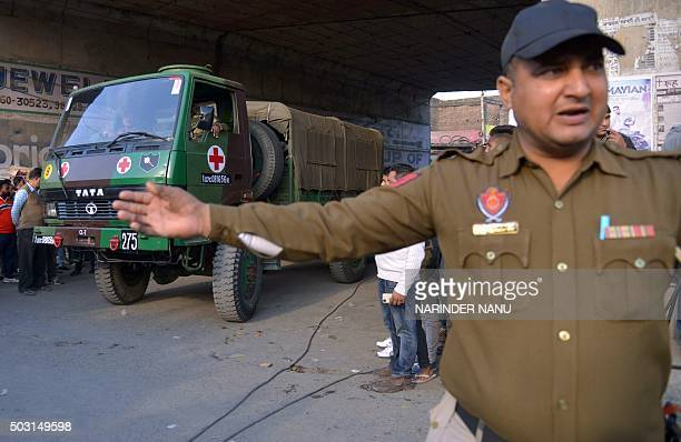 Indian police personnel escort an army ambulance outside an airforce base in Pathankot on January 2 during an ongoing attack on the base in the...