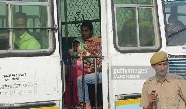 Indian police personnel keep watch as followers of selfstyled 'godman' Rampal Maharaj wait in a bus after leaving the ashram at Barwala in the...