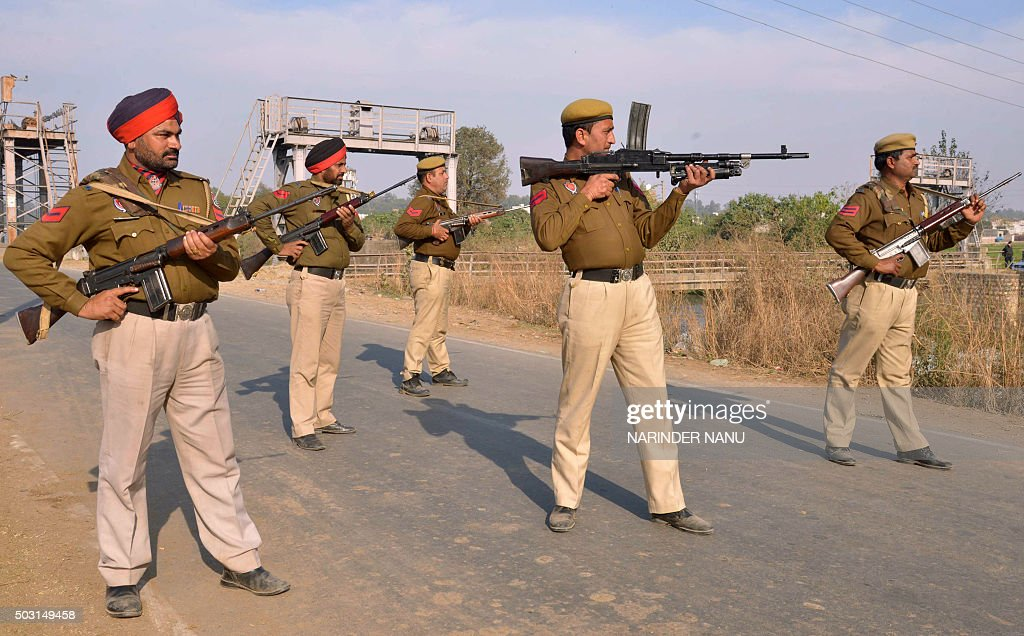 Indian police personnel stand alert outside an airforce base in Pathankot on January 2 during an ongoing attack on the base in the northern Indian...