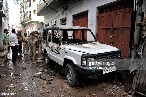 Indian police personnel stand beside a vehicle which was burnt during communal violence at Begum Bazar in Hyderabad on March 30 2010 Indian police...