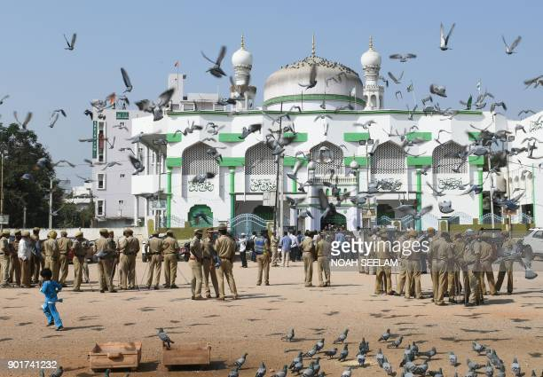 Indian police personnel stand guard in front of a mosque as members of Muslim organisations prepare to protest against the proposed 'Triple Talaq...