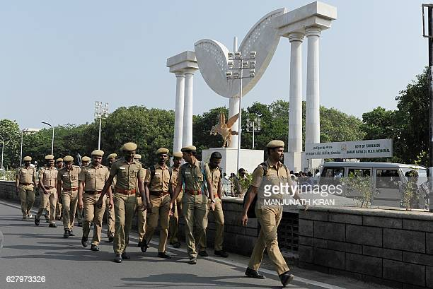 Indian police personnel take positions at the Anna Memorial where Tamil Nadu Chief Minister Jayalalithaa Jayaram will be buried in Chennai on...