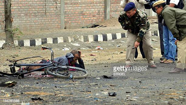 Indian police personnel talk to an injured person at the bomb blast site in Imphal India's northeastern state capital of Manipur on November 30 2011...