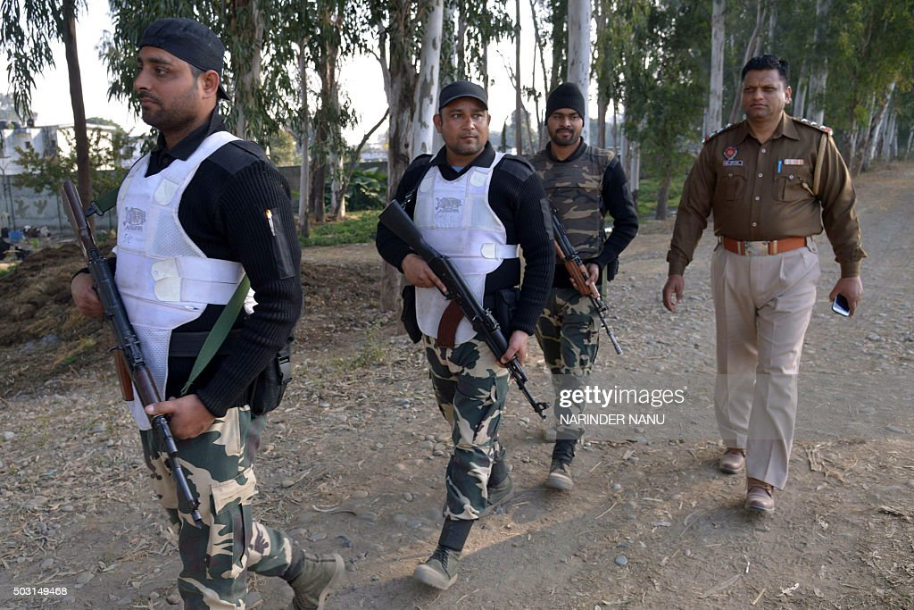 Indian police personnel walk outside an airforce base in Pathankot on January 2 during an ongoing attack on the base in the northern Indian state of..