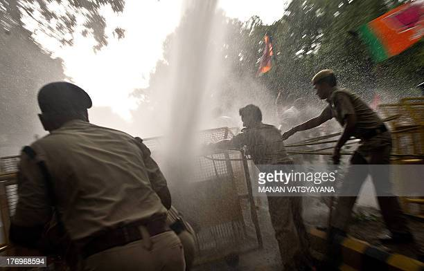 Indian police personnell use water canon to disperse activists from India's main opposition Bharatiya Janata Party during a protest against the Food...