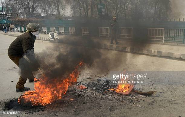 Indian police remove burning tyres during a protest in Srinagar on December 14 2015 Kashmiri protestors rallied against a new food safety act to be...