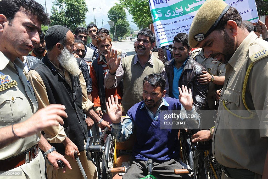 Indian police speak to members of the All Jammu and Kashmir Handicapped Association (AJKHA) as they march towards the civil secretariat which houses the office of chief minister Omar Abdullah, in Srinagar on May 20,2010. The All Jammu and Kashmir Handicapped Association (AJKHA) were demanding an increase in monthly pensions and free education for deaf and blind handicapped people . AFP PHOTO/Rouf BHAT