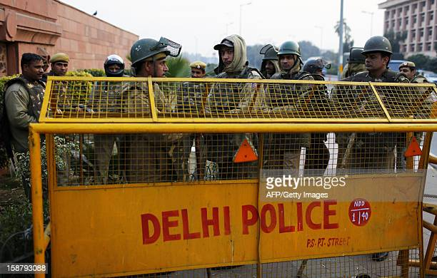 Indian police stand behind a barricade after the centre of the city was put into lock down in New Delhi on December 29 following the death of a rape...