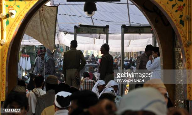 Indian police stand guard as devotees arrive at the Ajmer Sharif shrine in Ajmer on March 9 2013 Pakistan's Prime Minister Raja Pervez Ashraf is...